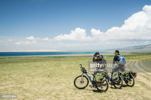 People ride bikes at the shore of Qinghai Lake Qinghai Lakethe sacred lake of the Tibetan Buddhism is the largest salt lake in China people cycling...