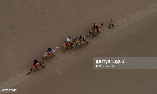 TOPSHOT People ride camels in the desert in Dunhuang China on July 18 as stage 10 of The Silkway Rally continues / AFP PHOTO / FRANCK FIFE