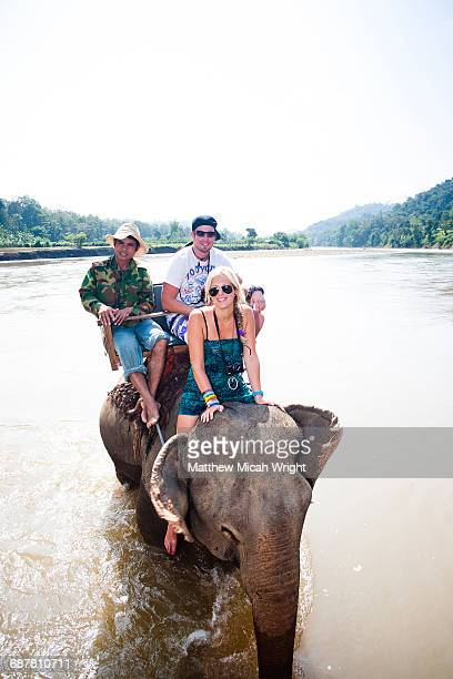 People ride down the river on an elephant.