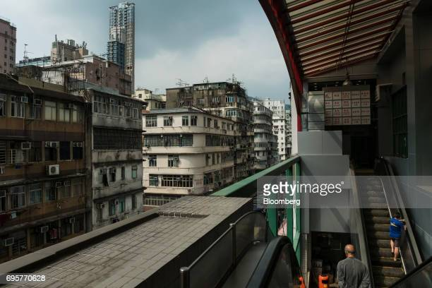 People ride escalators as residential buildings stand in the background in the Sham Shui Po district of Hong Kong China on Saturday April 29 2017...