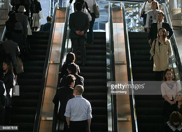 People ride escalators at a station in Tokyo Japan on Wednesday November 8 2006 Japan's economic growth probably failed to accelerate in the third...