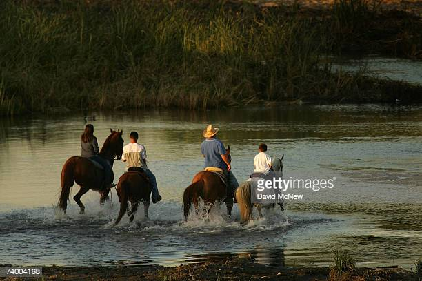 People ride horses across the San Gabriel River where the mosquitoes that can carry West Nile Virus are believed to have bred in previous seasons on...