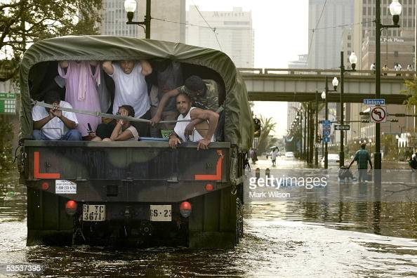 People ride in a back of a Military vehicle after being rescued from high water on Canal Street August 30 2005 in New Orleans Louisiana Thousands of...