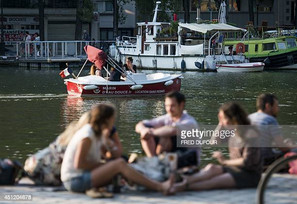 People ride in a rented motorboat as others sit on the quay of the Bassin de la Villette in northern Paris on June 25 2014 AFP PHOTO / FRED DUFOUR