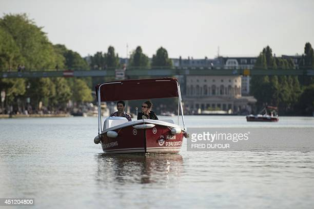 People ride in a rented motorboat in the Bassin de la Villette in northern Paris on June 25 2014 AFP PHOTO / FRED DUFOUR