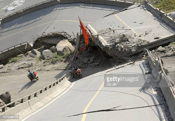 People ride motorbicycles past a collapsed bridge in one of the worst earthquakehit areas of Yingxiu town in Wenchuan county in China's southwestern...