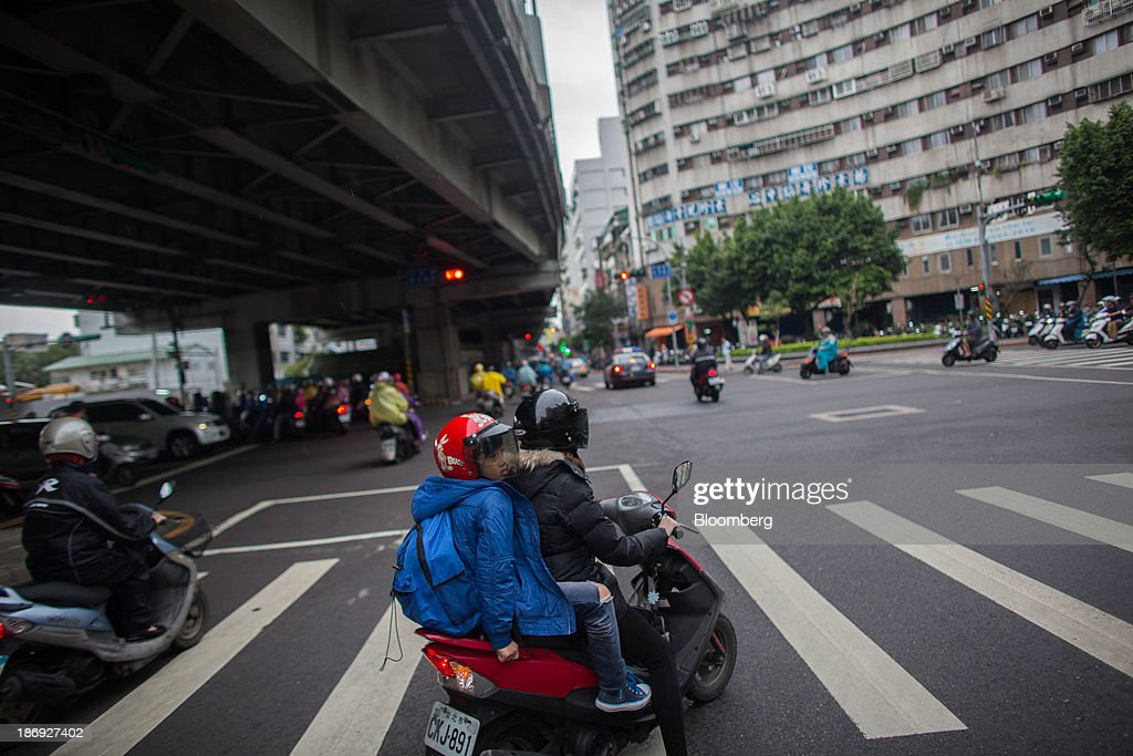 People ride motorcycles along a street in Taipei, Taiwan, on Monday, Nov. 4, 2013. Taiwans five-year bonds gained for the first time in four days, lowering the yield from a three-week high, after a report showed inflation cooled. The local dollar strengthened. Photographer: Lam Yik Fei/Bloomberg via Getty Images