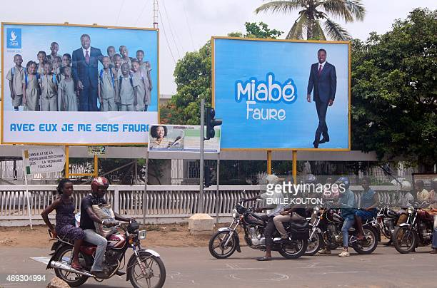 People ride motorcycles in front of posters displaying Togolese President Faure Gnassingbe on April 11 2015 in Lomé Togo officially began its...