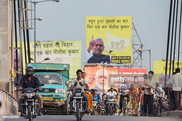 People ride motorcycles over a bridge past election billboard advertisements featuring images of Indian Prime Minister Narendra Modi and other party...