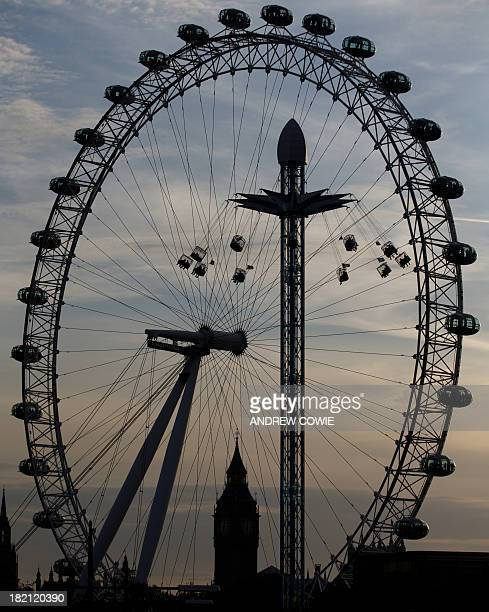 People ride on a fairground ride with the London Eye and Big Ben as a back drop as the sun sets in London on September 28 2013 AFP PHOTO / ANDREW...