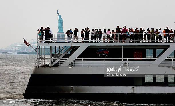 People ride on a ferry out to the Statue of Liberry off of the southern tip of Manhattan August 3 2008 in New York City Tourism is booming in New...