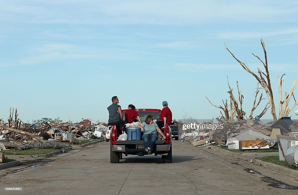 People ride on a truck through a neighborhood that was devastated by a tornado on June 2, 2013 in Moore, Oklahoma. Residents of Moore, Oklahoma continue to recover and sift through the remains of their homes two weeks after a devastating EF-5 tornado ripped through the town killing 24 people and destroying hundreds of homes and businesses.