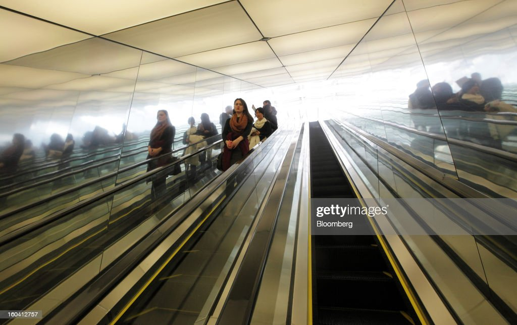 People ride on an escalator inside the Shanghai World Financial Center in the Pudong area of Shanghai, China, on Wednesday, Jan. 30, 2013. China's economic growth accelerated for the first time in two years as government efforts to revive demand drove a rebound in industrial output, retail sales and the housing market. Photographer: Tomohiro Ohsumi/Bloomberg via Getty Images