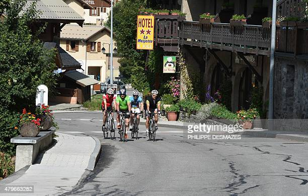 People ride on bicycles on June 6 2015 in La Grave eastern France on a road linking Grenoble to Briançon by the Lautaret pass which was cut by a...