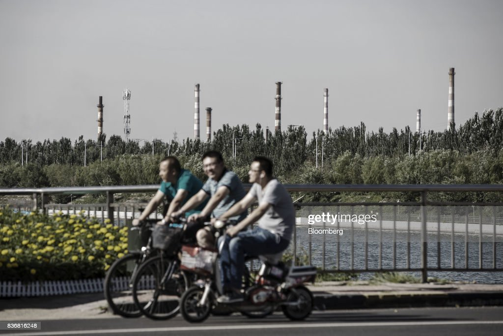 People ride on bicycles past the smoke stacks of factories and power plants in Baotou, Inner Mongolia, China, on Friday, Aug. 11, 2017. China's economy showed further signs of entering a second-half slowdown, as curbs on property, excess borrowing and industrial overcapacity began to bite. Photographer: Qilai Shen/Bloomberg via Getty Images