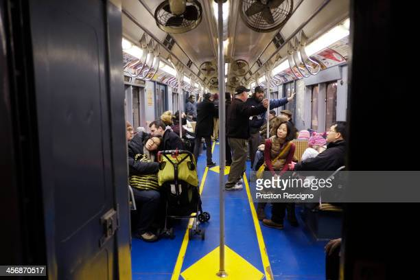 People ride on the Metropolitan Transit Authority 'Nostalgia' vintage subway train on December 15 2013 in New York City The MTA is running their...