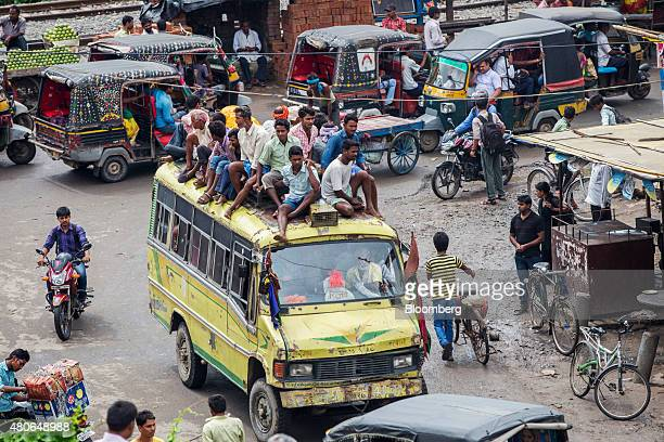 People ride on the roof of a commuter bus in Patna Bihar India on Saturday July 11 2015 Anyone placing bets on whether Indian central bank Governor...