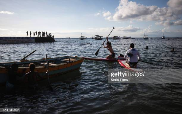 People ride paddle boards as other gather in the Barra neighborhood in an upscale section of the city on April 19 2015 in Salvador Brazil