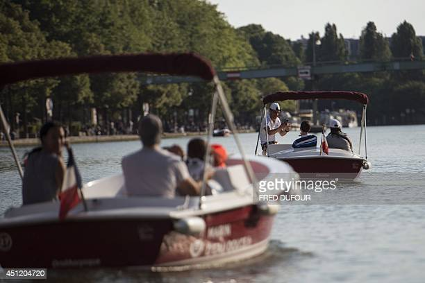 People ride rented motorboats in the Bassin de la Villette in northern Paris on June 25 2014 AFP PHOTO / FRED DUFOUR