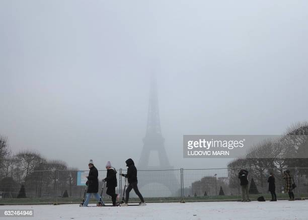 People ride scooters through light snowfall in front of the Eiffel Tower on January 23 2017 in Paris / AFP / Ludovic MARIN