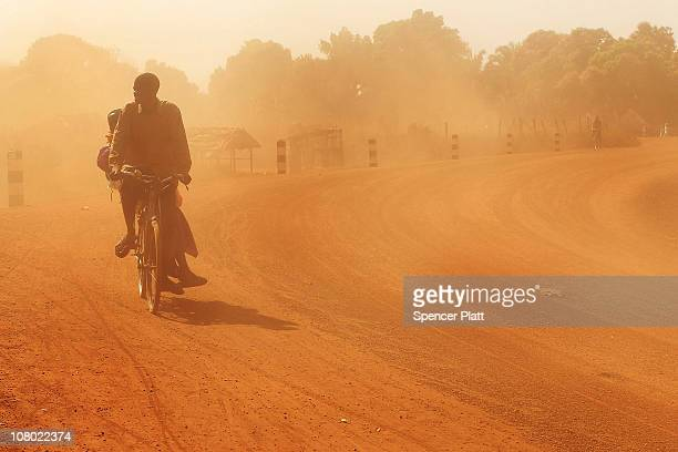 People ride their bicycles down a street January 13 2011 in the town of Yambio south Sudan Yambio a poor and isolated town near the borders of...