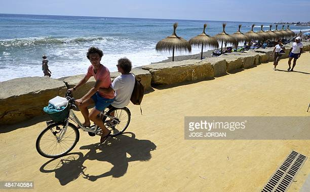 People ride their bikes along a dirt track in Marbella's Puerto Banus marina on August 21 included in the first stage of the Vuelta a Espana cycling...