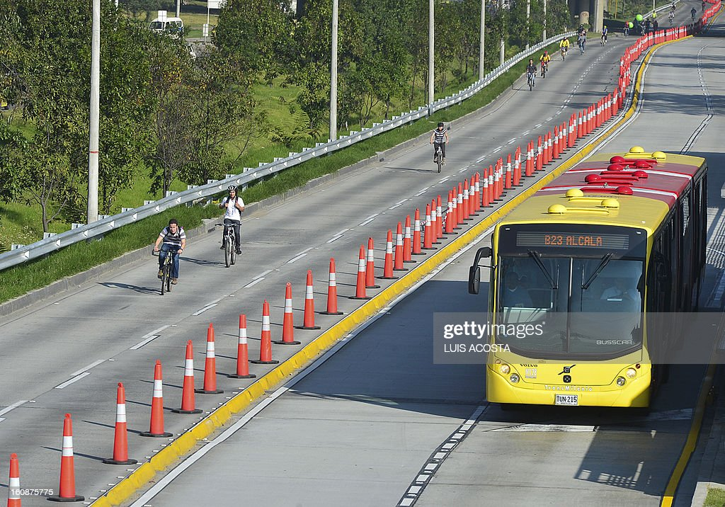 People ride their bikes along a freeway during Car Free day in Bogota, Colombia, on February 7, 2013. Residents of Bogota are asked not to use their cars in an attempt to reduce environmental pollution. AFP PHOTO/ Luis Acosta