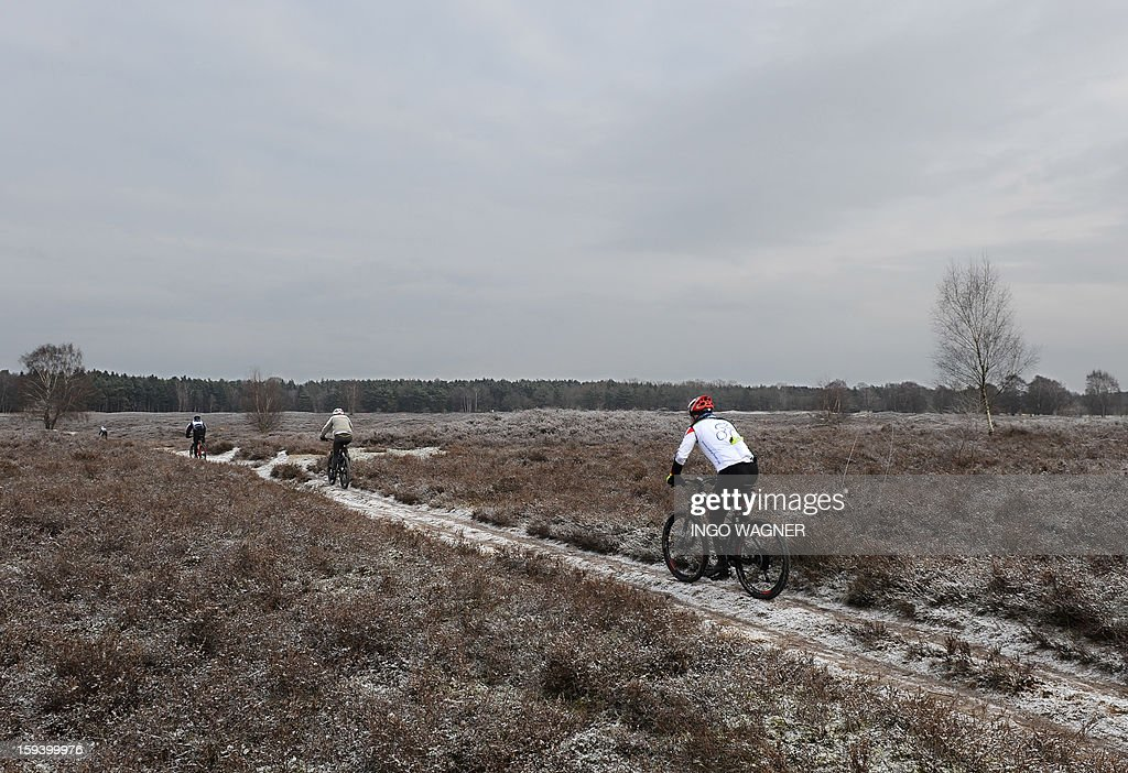 People ride their bikes on a white frosted field near, Wildeshausen, northern Germany, on January 13, 2013.Meteorologists forecast falling temperatures and return of winter in Germany.