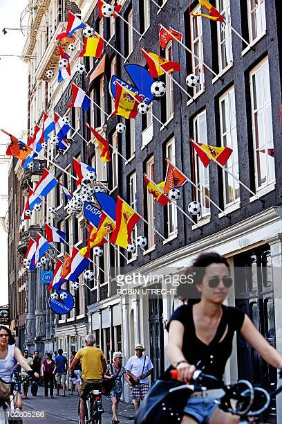 People ride their bikes under Dutch and Spanish flags on a building in Amsterdam on July 10 2010 a day before the 2010 football World Cup final in...