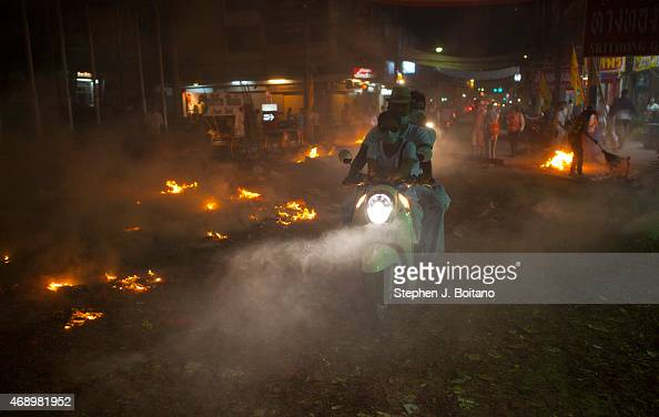 People ride through the smokey burning streets at the Phuket Vegetarian Festival in Phuket Town Thailand
