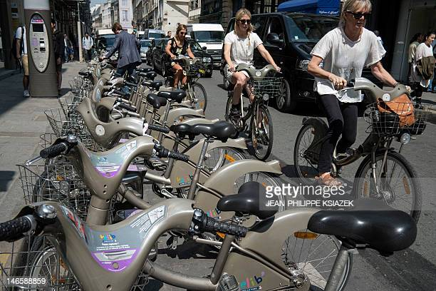 People ride 'Velib' bicycles next to a bikesharing station on June 20 in Paris With over 20000 bikes covering Paris in 1800 bike stations 'Velib' is...