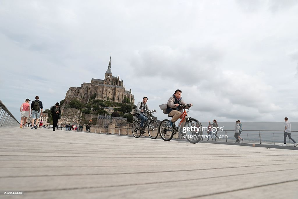 People rides near Le Mont-Saint-Michel (background), on June 29, 2016, three days before the start of the 103rd edition of the Tour de France cycling race. The 2016 Tour de France will start on July 2 in the streets of Le Mont-Saint-Michel and ends on July 24, 2016 down the Champs-Elysees in Paris. / AFP / KENZO