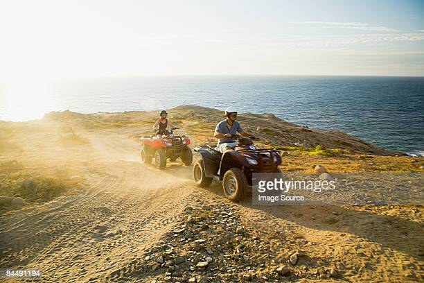 People riding all terrain vehicles