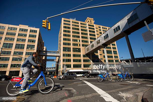 People riding bicycles from the CitiBike bike sharing program pass the Dumbo Heights campus in the Brooklyn borough of New York US on Thursday Oct 15...