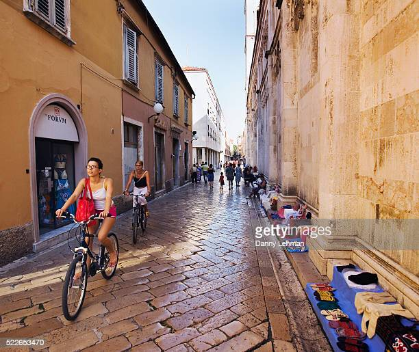 People Riding Bikes in Stone Lined Street