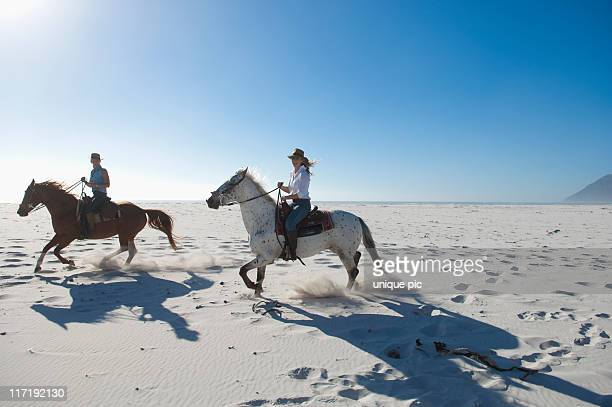 2 people riding horses in the sand