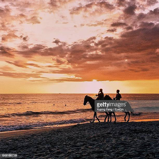 People Riding Horses On Shore At Beach Against Sky During Sunset