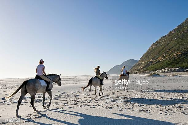 3 people riding horses on the beach