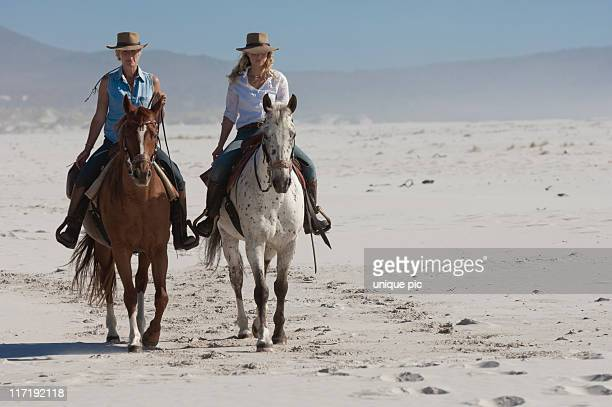 2 people riding horses on the beach