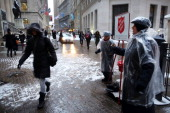 People rings bells to raise money for the Salvation Army during a morning snow storm on December 17 2013 in New York City The metro area is expecting...