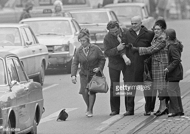 people road traffic older man is shocked after a road accident some passersby help him going up aged 70 to 80 years
