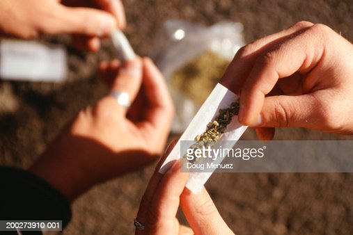 People rolling joints on street, close-up of hands