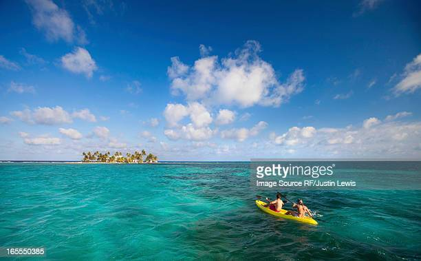 People rowing canoe in tropical water