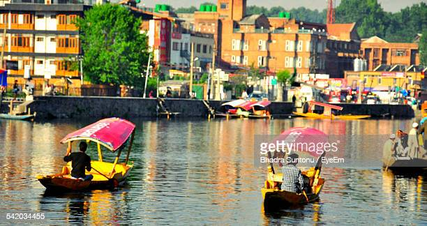 People Rowing Shikharas On Dal Lake Against Buildings