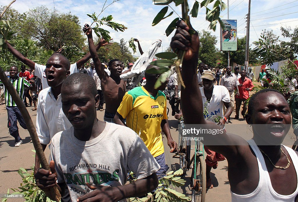 People run along a street waving twigs and chanting, on October 30, 2012 in the western Kenya's lakeside town of Kisumu during the second day of unrest following the murder of a prominent local politician. Violent protests erupted after Shem Onyango Kwega, a candidate for a parliamentary seat in Kisumu in general elections due in March, was killed by unidentified armed men on October 30 while driving in town. Kwega, the local branch chairman of Prime Minister Raila Odinga's Orange Democratic Movement (ODM), was shot in the head and later died at the hospital while his wife was seriously wounded in the same attack. Four people were wounded by bullets during confrontations with the police and a police officer was hit by a stone hurled by the protesters.