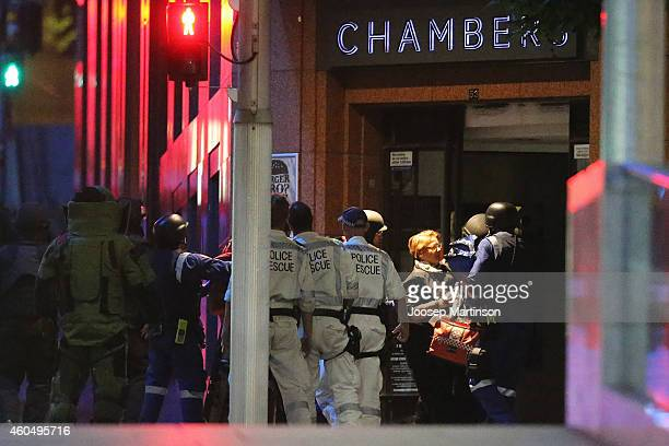 People run as police surround the Lindt Cafe Martin Place during a hostage standoff on December 16 2014 in Sydney Australia Police stormed the Sydney...