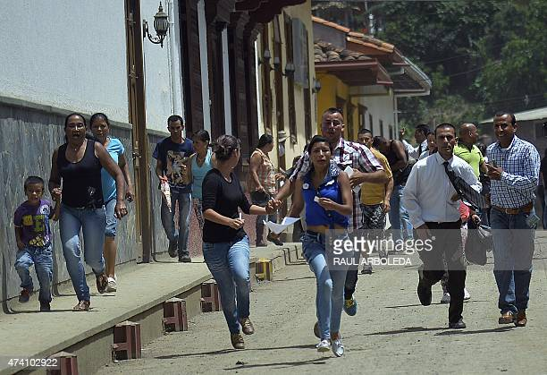 People run as the alarm of a possible landslide sounds in Salgar Municipality Antioquia department Colombia on May 20 2015 A massive landslide tore...