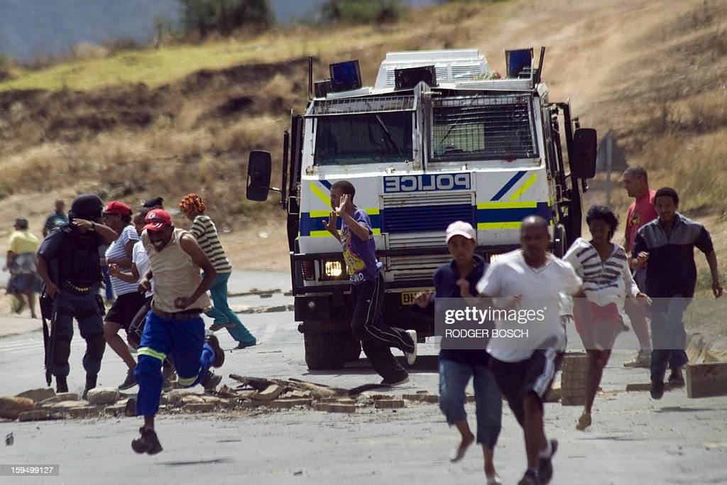 People run away as a South African Police Services armoured vehicle approaches a road-block during an illegal strike by farmworkers, on January 14, 2012 in Villiersdorp, a small farming town about 100Km North of Cape Town, South Africa. The farm workers have said that they they will not return to work on the fruit growing region's farms until they receive a daily wage of at least R150($17) per day. BOSCH