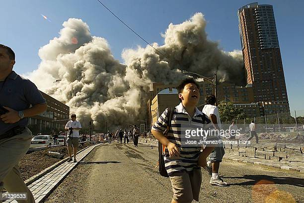 People run away as the North Tower of World Trade Center collapses after a hijacked airliner hit the building September 11 2001 in New York City