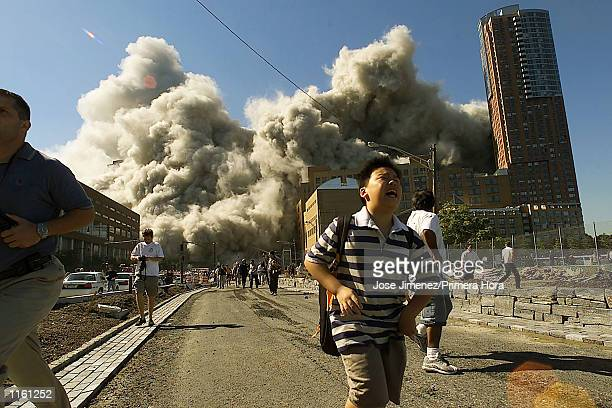 People run away as the second tower of World Trade Center crumbles down after a plane hit the building September 11 2001 in New York City